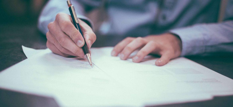 Mężczyzna podpisujący dokumenty dotyczące założenia prostej spółki akcyjnej